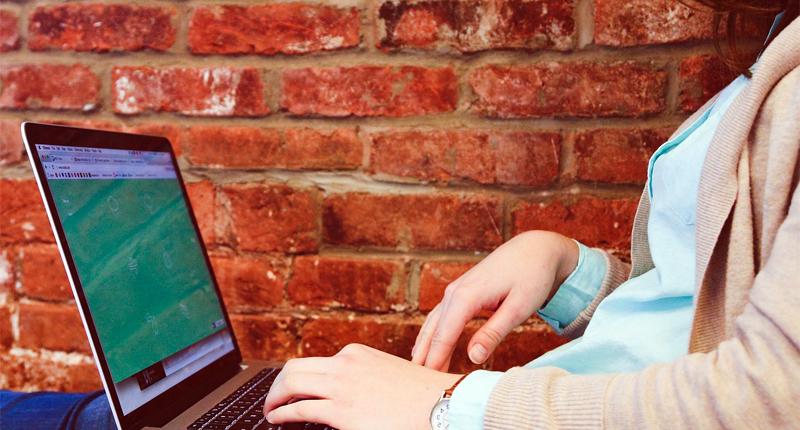 Frau mit Laptop sitzt auf Bank